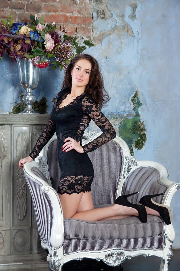Meisje in zwarte seksualiteitkleding op stoel royalty-vrije stock afbeeldingen