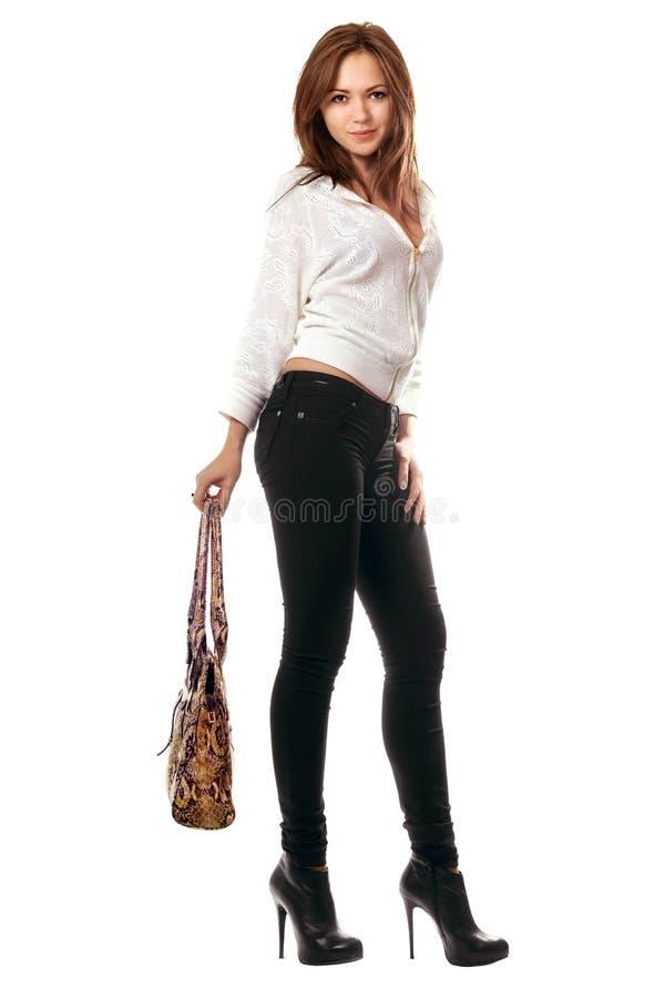 Meisje in zwarte strakke jeans met een handtas stock afbeeldingen