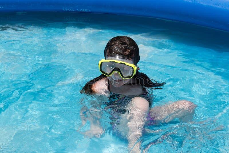 Meisje in zwemmend masker in binnenplaatspool stock foto's