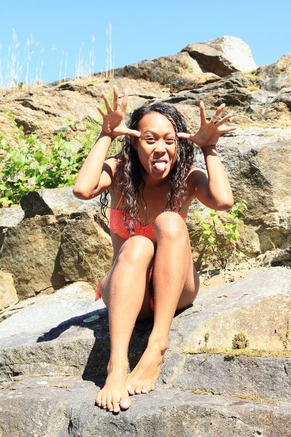 Meisje in zwempak op rots stock afbeeldingen
