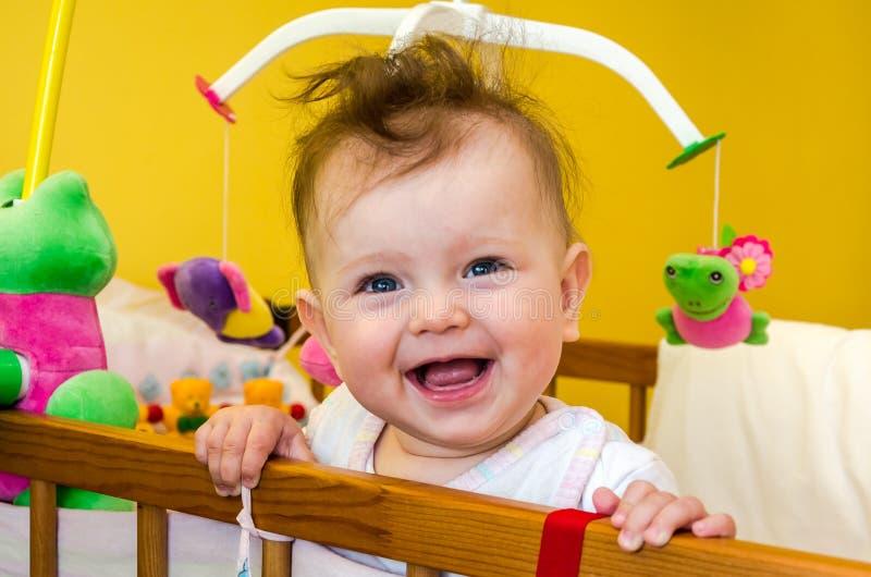 Meisjebaby het glimlachen zitting in haar bed royalty-vrije stock afbeeldingen