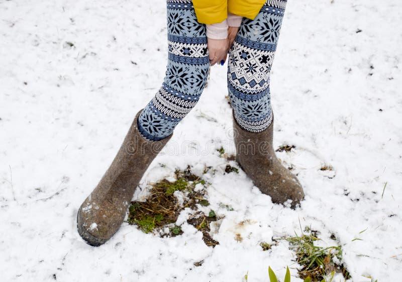 Meisjebenen in warme broek en gevoelde laarzen Het meisje in de sneeuw in de winter stock foto's