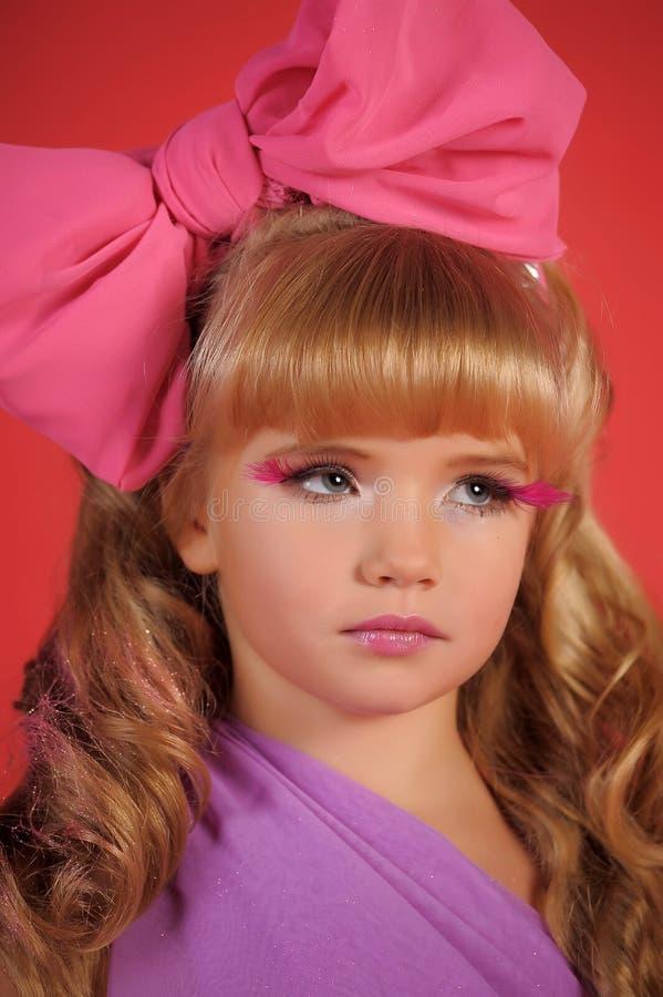 Meisjeblonde met een grote boog en roze wimpers royalty-vrije stock afbeelding