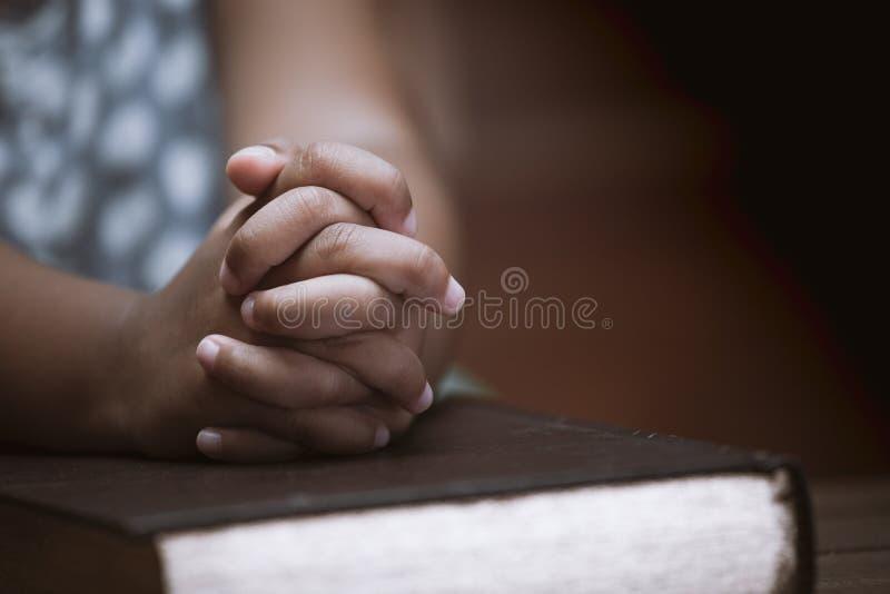 Meisjehanden in gebed op een Heilige Bijbel in kerk worden gevouwen die royalty-vrije stock foto's
