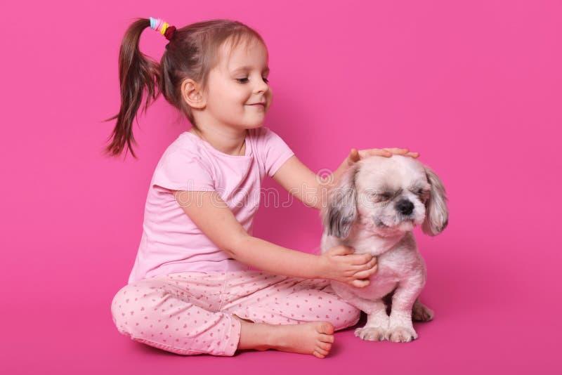 Meisjehuisdieren pekingese haar terwijl het zitten met gekruiste benen op vloer Het aanbiddelijke kind houdt van haar huisdier He stock foto