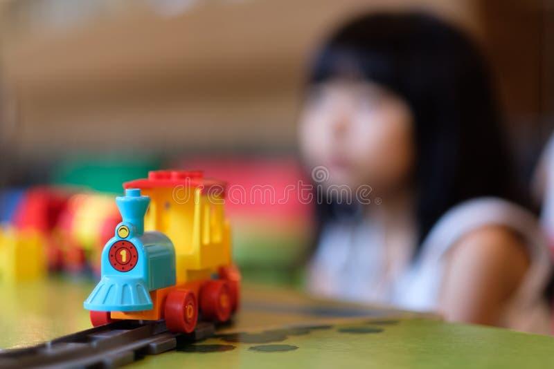 Meisjejong geitje het spelen met treinstuk speelgoed stock fotografie