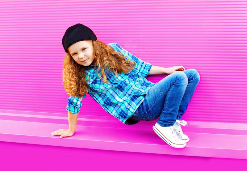 Meisjekind die in stad op kleurrijk roze dansen stock foto