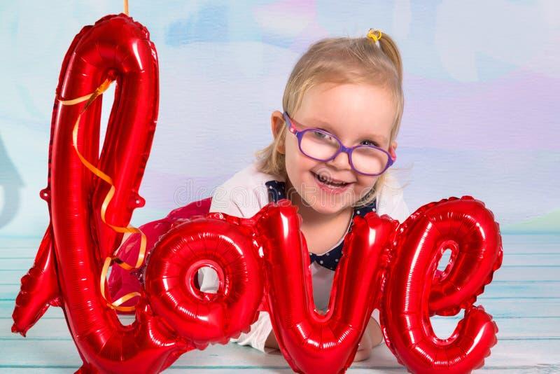 Meisjepeuter met het rode teken van de hart balloonand liefde Het concept van de Dag van valentijnskaarten royalty-vrije stock afbeeldingen
