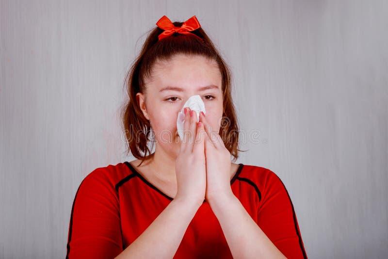 Meisjes afvegende en schoonmakende neus met weefsel op haar hand royalty-vrije stock afbeeldingen