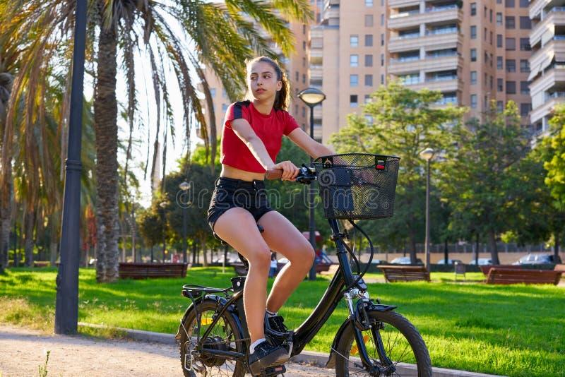Meisjes berijdende e-fiets in een stadspark royalty-vrije stock fotografie