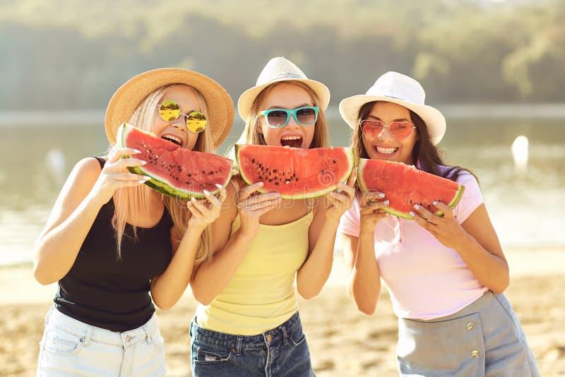 Meisjes bij een partij die een watermeloen op het strand eten stock foto