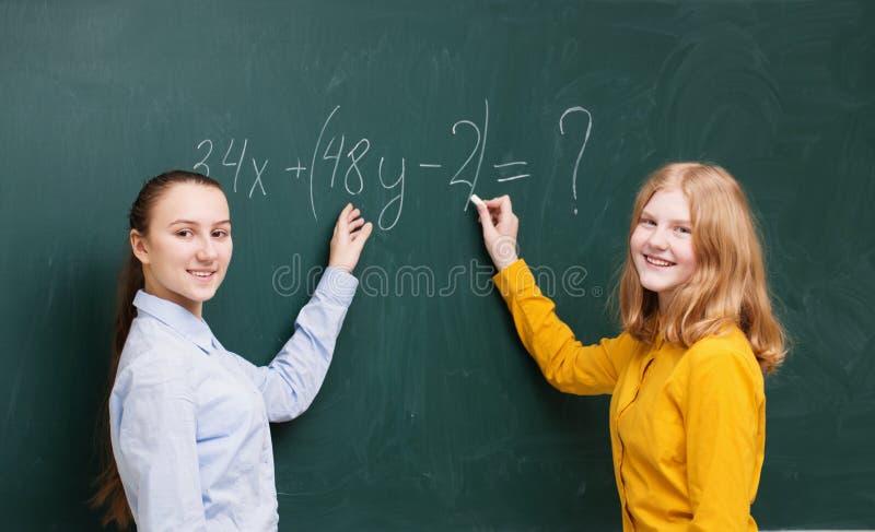 Meisjes bij het bord in wiskundeklasse stock foto