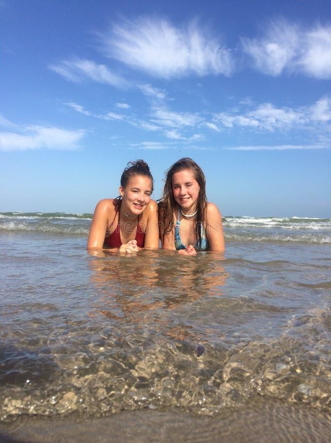 Meisjes bij strand in golven royalty-vrije stock fotografie