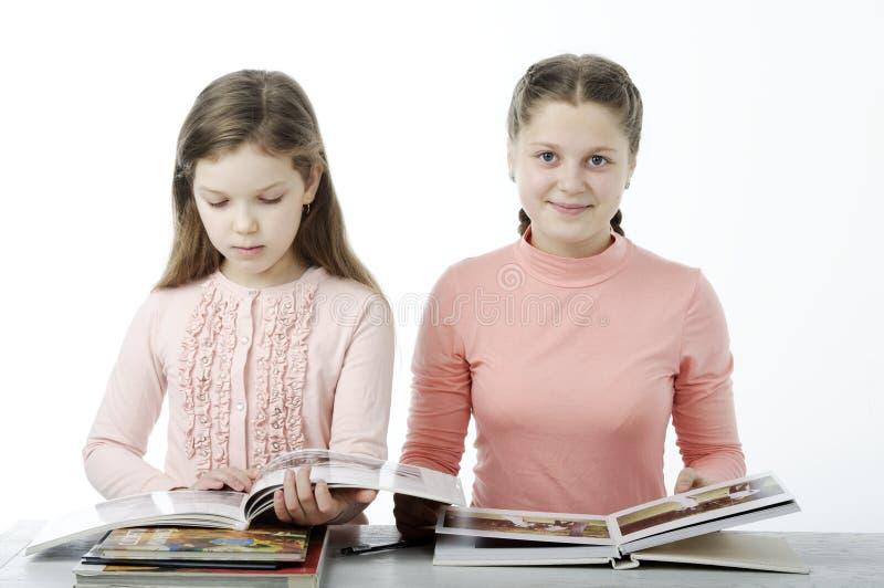 Meisjes boeken worden gelezen bij de lijst aangaande wit dat royalty-vrije stock fotografie
