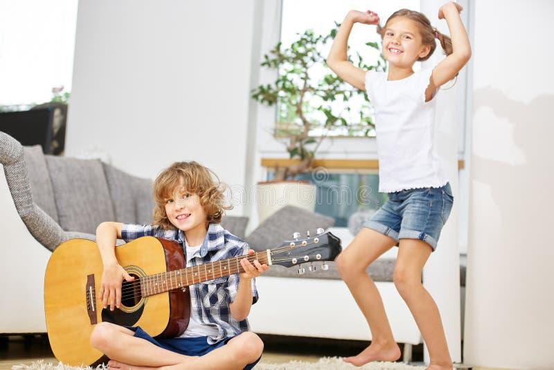 Meisjes dansen en jongen die de gitaar spelen stock afbeeldingen