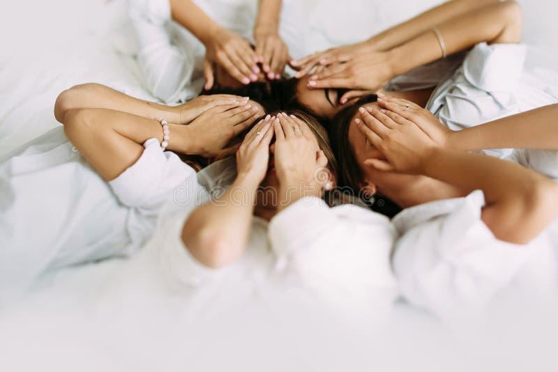 Meisjes in de witte overhemden op het bed stock foto