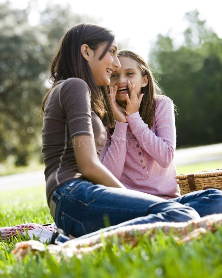 Meisjes die aan elkaar bij picknick in park fluisteren royalty-vrije stock foto's
