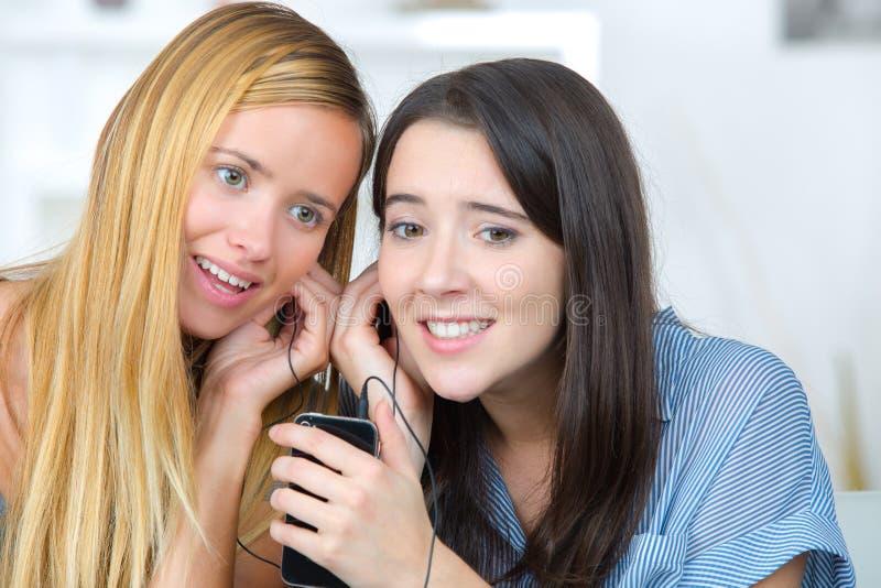Meisjes die aan muziek luisteren stock afbeeldingen