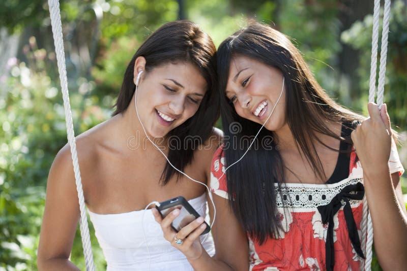 Meisjes die aan muziek luisteren stock afbeelding