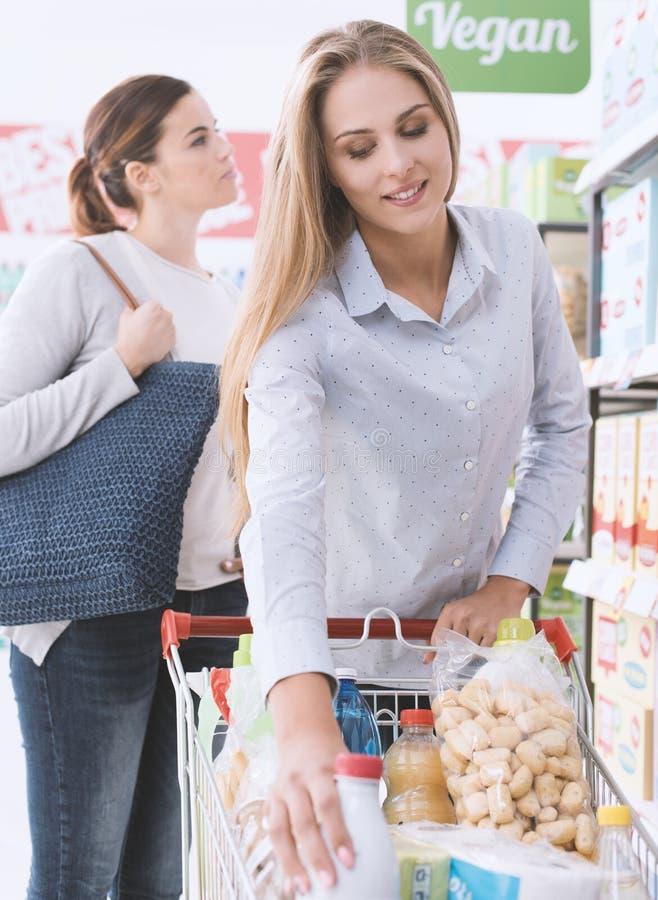 Meisjes die bij de supermarkt winkelen stock afbeelding