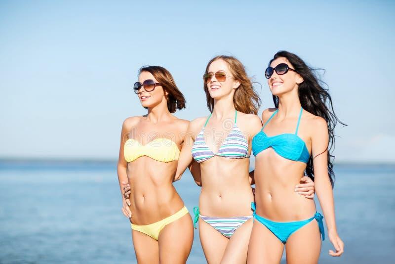 Meisjes die in bikini op het strand lopen royalty-vrije stock afbeeldingen