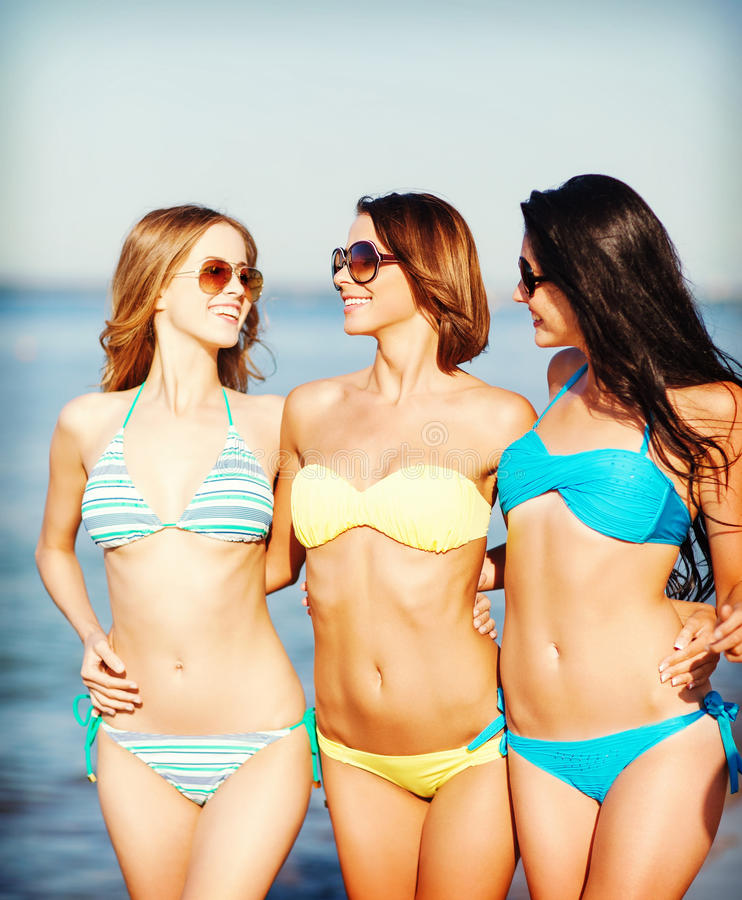 Meisjes die in bikinis op het strand lopen royalty-vrije stock afbeelding