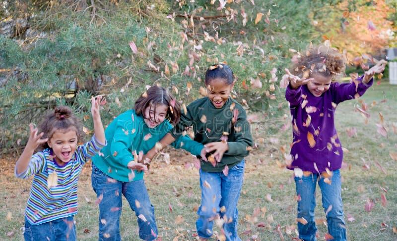 Meisjes die in Bladeren spelen stock foto
