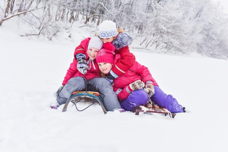 Meisjes die dag van het spelen in de winterbos genieten royalty-vrije stock fotografie