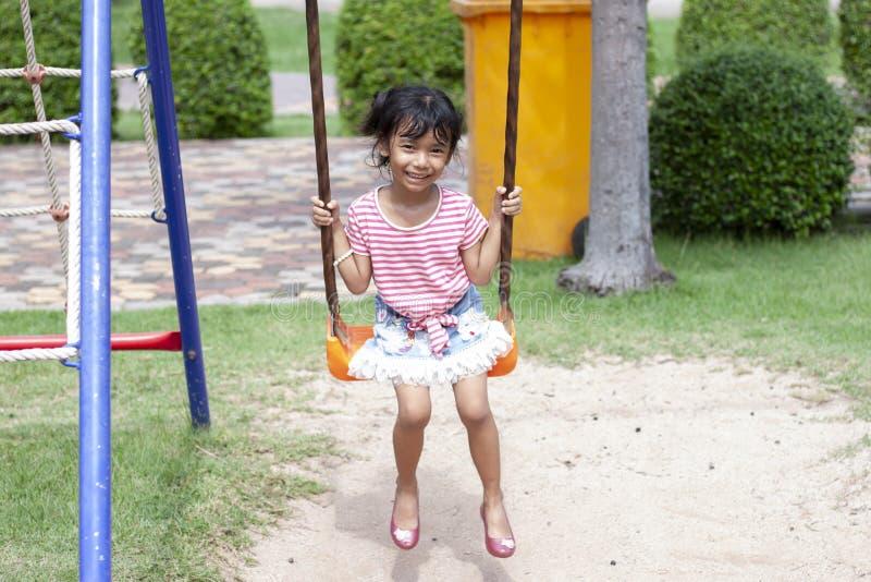 Meisjes die in de schommeling in de zonneschijn met een gelukkige glimlach zitten royalty-vrije stock afbeeldingen