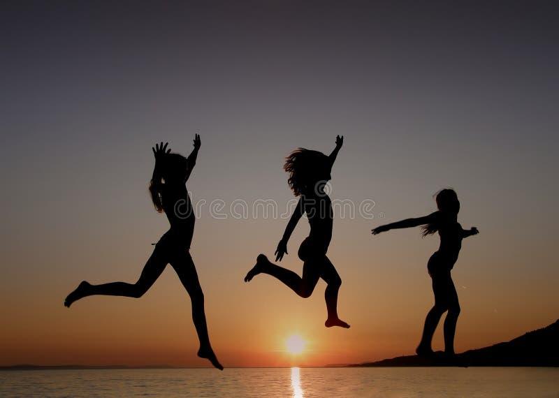 Meisjes die in de zonsondergang op zee springen stock afbeeldingen