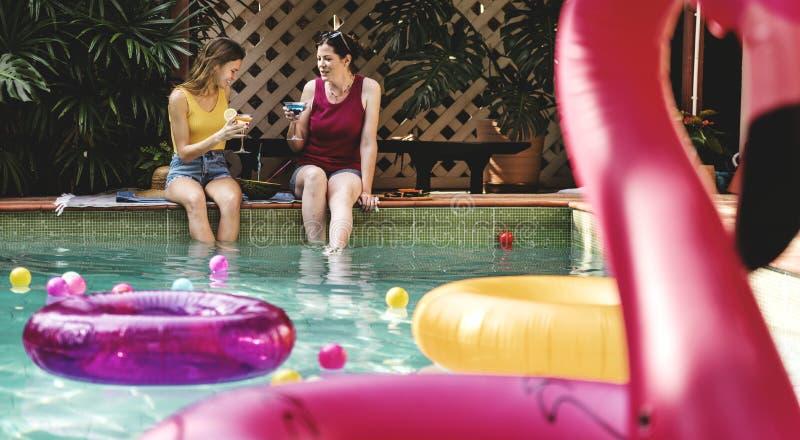 Meisjes die door het zwembad ontspannen royalty-vrije stock foto