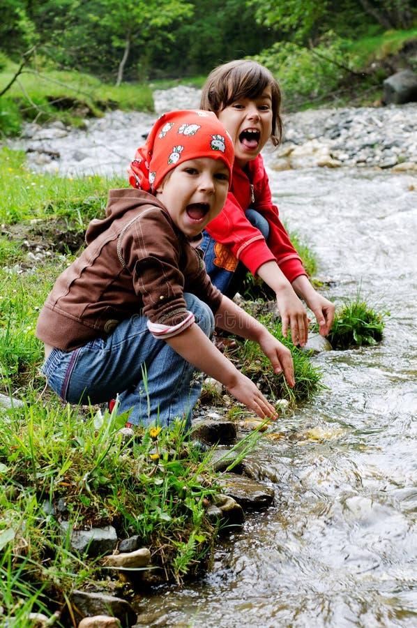 Meisjes die door rivier spelen stock foto's