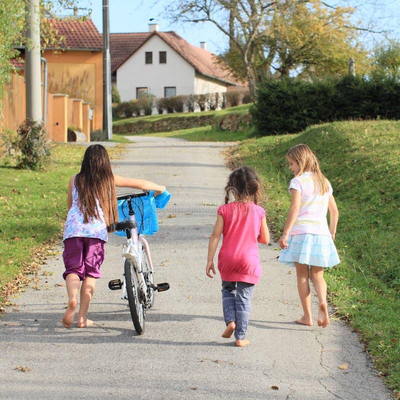 Meisjes die en een fiets lopen duwen stock foto's
