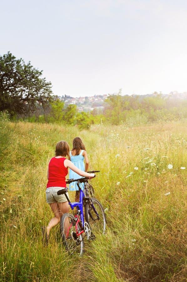 Meisjes die fietsen op gebied lopen stock foto