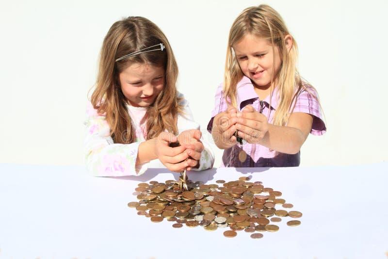 Meisjes die geld pooring door handen stock foto