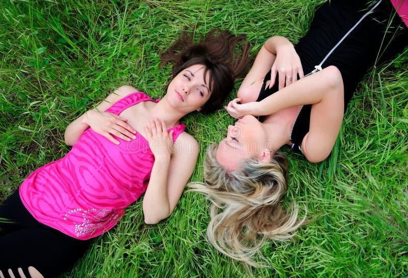 Meisjes die in gras leggen stock afbeeldingen