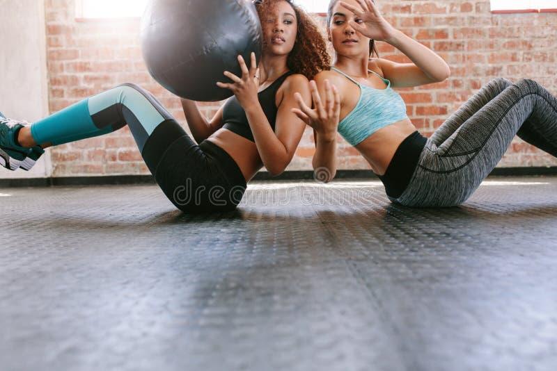 Meisjes die in gymnastiek met geneeskundebal uitwerken royalty-vrije stock fotografie