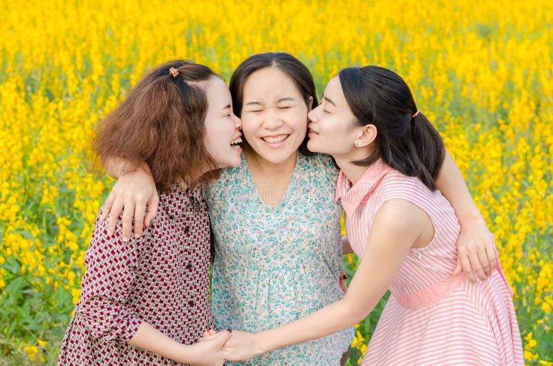 Meisjes die hun moeder op bloemgebied kussen royalty-vrije stock fotografie