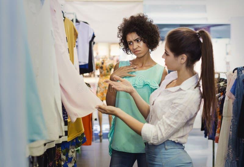 Meisjes die kleding kiezen bij de kledingsopslag royalty-vrije stock afbeelding