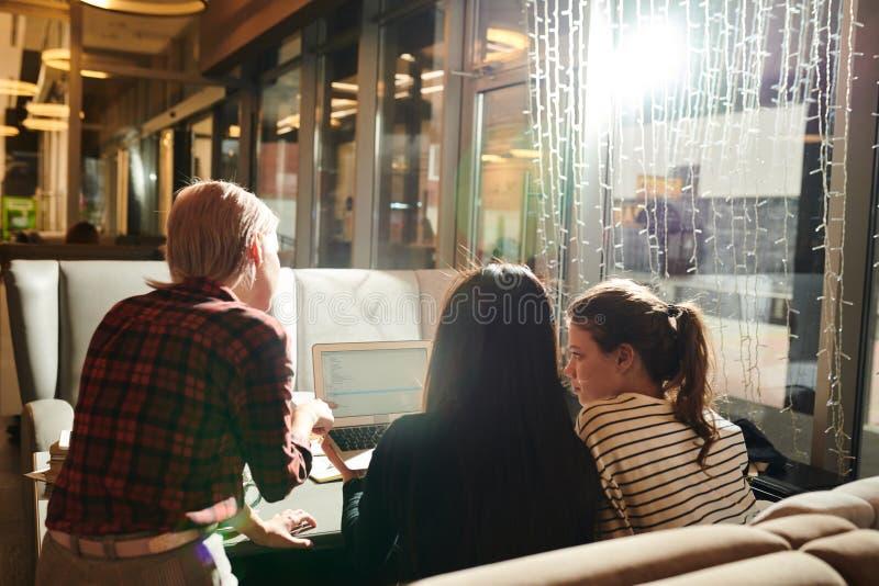 Meisjes die laptop in koffie met behulp van royalty-vrije stock afbeeldingen