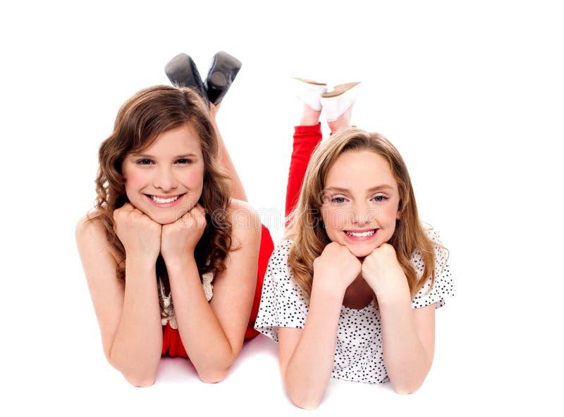 Meisjes die met handen op kin stellen. Het liggen op vloer royalty-vrije stock afbeelding