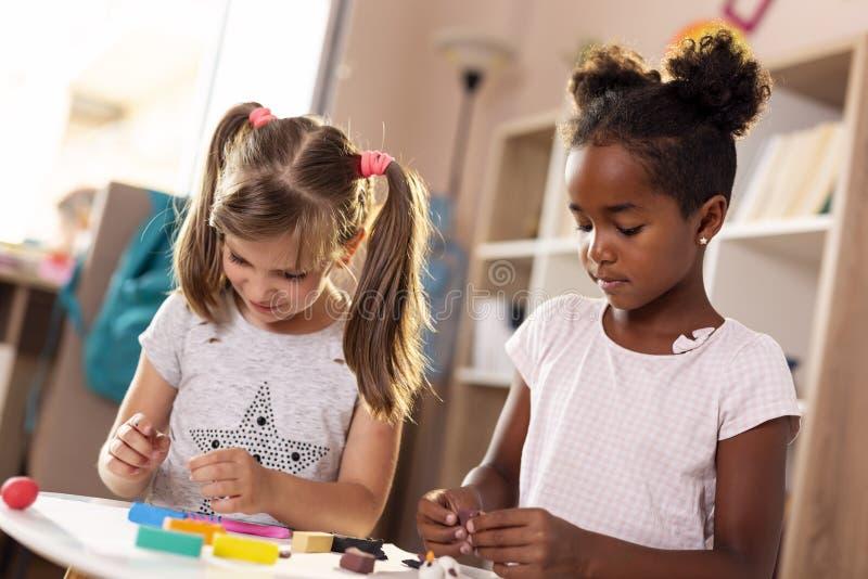 Meisjes die met kleurrijke plasticine spelen royalty-vrije stock afbeeldingen