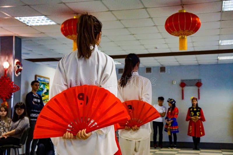 Meisjes die met rode ventilators in viering van het Chinese Nieuwjaar dansen royalty-vrije stock foto