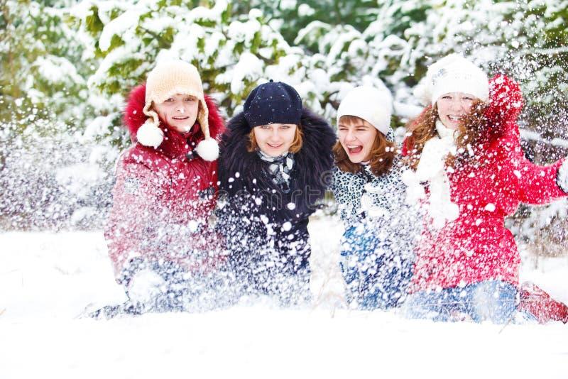 Meisjes die met sneeuw in park spelen stock fotografie