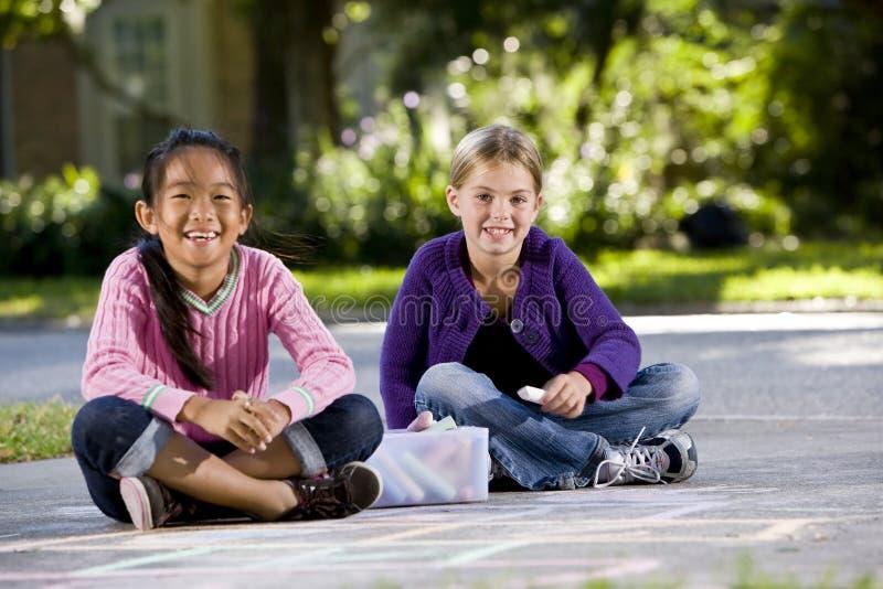 Meisjes die met stoepkrijt spelen royalty-vrije stock afbeeldingen