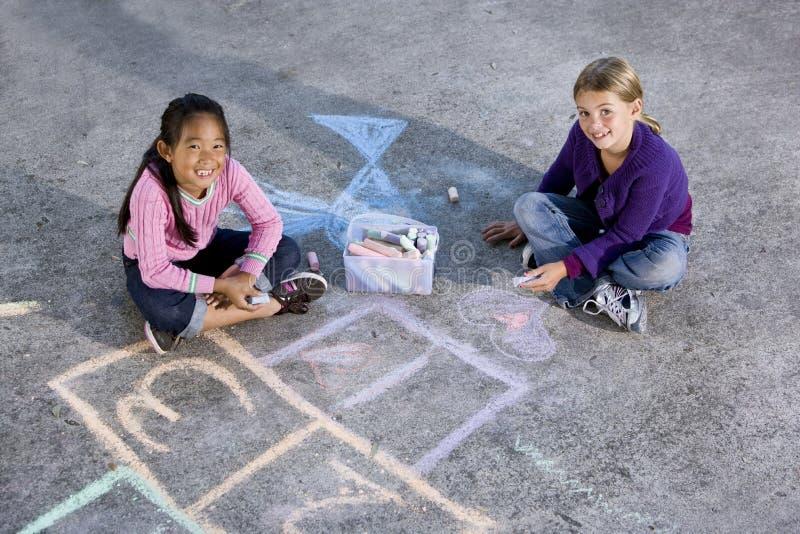 Meisjes die met stoepkrijt spelen stock fotografie