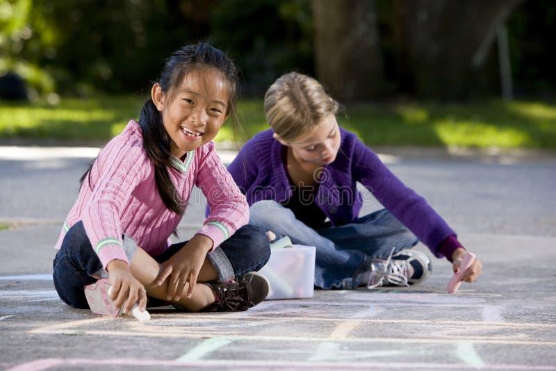 Meisjes die met stoepkrijt spelen stock foto