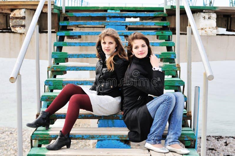 Meisjes die op de treden zitten royalty-vrije stock afbeelding