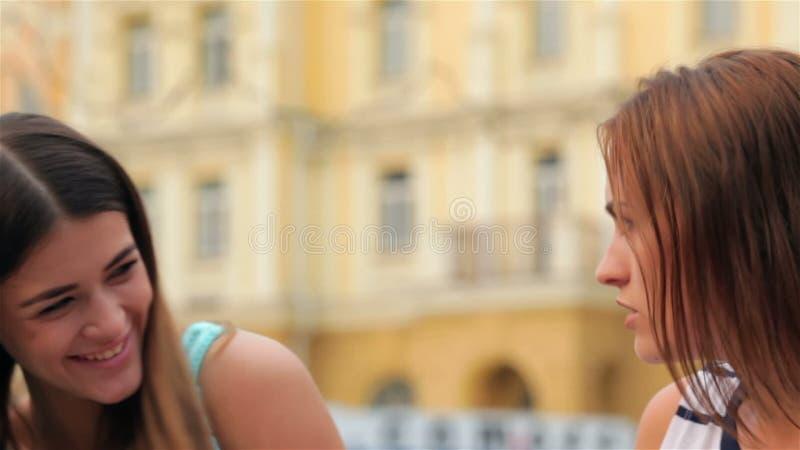 Meisjes die op een bank fluisteren