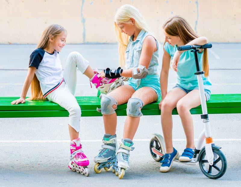 Meisjes die op rollerskates zetten stock afbeelding